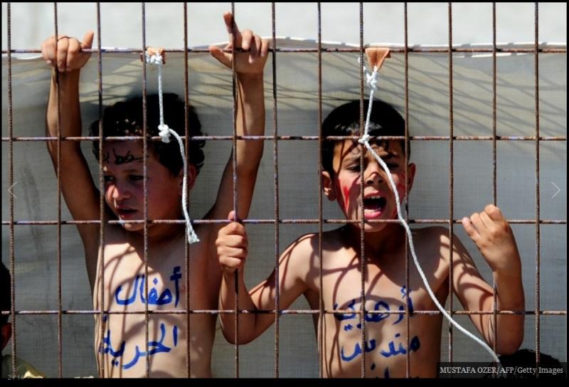 لاجئان سوريان يرددان شعارات خلال احتجاج من وراء السياج في مخيم الهلال الأحمر التركي، على بعد 30 كيلو متر من الحدود السورية، في 17 يونيو/ حزيران 2011.