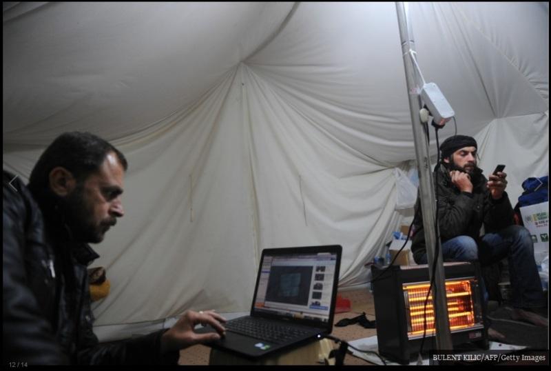 لاجئ سوري يستخدم أجهزة الكمبيوتر المحمولة والهواتف المحمولة للاتصال في مخيم بالقرب من البلدة التركية الحدودية Yayladagi في 6 ديسمبر/ كانون الأول 2011. في 1 ديسمبر علقت دمشق اتفاق عام 2004 للتجارة مع تركيا، واحدة من أقرب الشركاء الاقتصاديين لسوريا، كما أعلنت الجامعة العربية عن عدد من العقوبات ضد نظام الأسد.