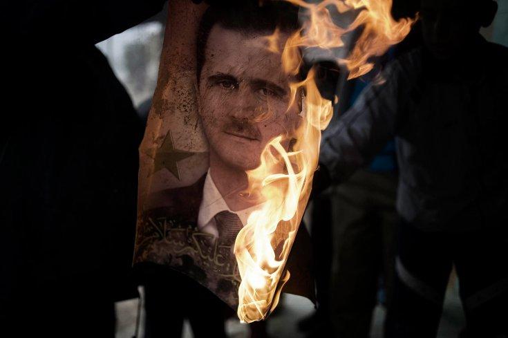 عنصر من الجيش السوري الحر يحرق صورة لبشار الأسد في بلدة القصير 25 كانون الثاني /يناير 2012