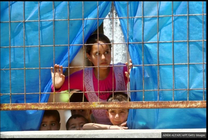 ينظر الأطفال اللاجئون السوريون من خلال الجدار إلى المخيم في بلدة Yayladagi على الحدود التركية في محافظة Hatay في 26 يونيو/ حزيران 2011. بالرغم من حقيقة أن نحو 12,000 لاجئ سوري احتموا في تركيا في ذلك الوقت، إلا أنه لم يمتثل سوى بضع مئات إلى دعوات الأسد للعودة إلي منازلهم في ذلك الصيف.