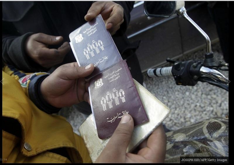 لاجئون سوريون يحملون جوازات سفرهم بانتظار دورهم للحصول على مساعدات إنسانية عند مدخل أحد المنظمات غير الحكومية في المنطقة الحدودية لوادي خالد، شمال لبنان، يوم 26 فبراير/ شباط 2012.