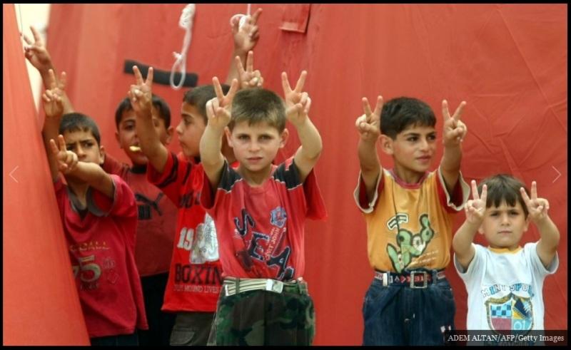 لاجئون سوريون أطفال يرسمون رموز السلام من وراء سياج المخيم بالقرب من الحدود التركية Yayladagi.