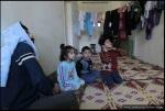 عائلة سورية لاجئة تجلس في قاعة دافئة في مخيم تم إنشاؤه جزئياً في مدينة المفرق في 20 فبراير/شباط 2012، بالقرب من الحدود الشمالية الأردنية مع سوريا.