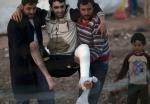 16- أصدقاء يحملون لاجئاً سورياً جريحاً داخل مخيمهم في Reyhanli، تركيا، يوم 20 آذار/مارس. (برهان أوزبيليجي Burhan Ozbilici /أسوشييتد برس).