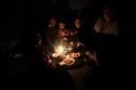 21- أفراد من عائلة سورية هربوا من العنف في حي بابا عمرو في مدينة حمص الثائرة، يتناولون عشاءهم في غرفتهم خلال انقطاع التيار الكهربائي داخل مدرسة تحولت إلى مركز للاجئين في منطقة وادي خالد على الحدود اللبنانية السورية شمال لبنان يوم 15 آذار/ مارس. حسب مسؤولين في الأمم المتحدة وآخرين محليين، عبر الحدود إلى لبنان أكثر من 1500 سوري، معظمهم من النساء والأطفال خلال الأسابيع الأخيرة. (جوزيف عيد/ AFP).