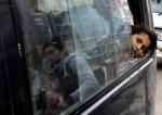 25- فتاة سورية هربت من العنف في قرية القصير السورية تنظر إلى الخارج من نافذة حافلة عند وصولها إلى مدينة عرسال اللبنانية في وادي البقاع بعد عبور الحدود الشمالية للبنان مع سوريا يوم 26 آذار/ مارس. (جوزيف عيد/ AFP).