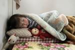 26- فتاة سورية هربت من العنف في سوريا تنام مع لعبة في منزل للاجئين في مدينة عرسال اللبنانية في وادي البقاع يوم 26 آذار/مارس. (جوزيف عيد/ AFP).