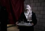 27- لاجئة هربت من العنف في سوريا تحمل صينية الشاي في منزلها المؤقت في مخيم الحسين للاجئين الفلسطينيين في عمان يوم 7 آذار/مارس عشية اليوم العالمي للمرأة. (علي جاركجي  Ali Jarekji/رويترز).