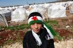 31- محمد (12 عاماً)، لاجئ سوري يرتدي وشاحاً بألوان علم الاستقلال السوري، يقف خارج مخيم Reyhanli  للاجئين في مقاطعة Hatay  على الحدود التركية السورية يوم 17 آذار/ مارس. ارتفع عدد السوريين الذين عبروا الحدود خلال الأسابيع القليلة الماضية بشكل مأساوي الآن بمعدل 200 إلى 300 لاجئ يصلون إلى تركيا كل يوم. عبر الحدود هذا الأسبوع 1000 شخص خلال 24 ساعة فقط، وهو الرقم الأعلى منذ أول دفعة من اللاجئين في الصيف الماضي. يعيش الآن حوالي 15,000 لاجئ سوري مسجل في خيام داخل تركيا، مشكليّن تقريباً نصف عدد الأشخاص الذين قدرتهم الأمم المتحدة بـ 34,000 نازح من سوريا منذ بداية النزاع قبل عام. (مراد سيزر Murad Sezer/رويترز).