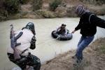 أعضاء في الجيش السوري الحر ينقلون أسلحة وأدوية وأفراد عبر نهر بالقرب من الجنودية، محافظة إدلب، سوريا.