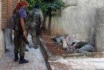 يفتش المتمردون في بيت بحثاً عن موالين للأسد في حارم شمال البلاد. يقف أحدهم ويحدّق في الجثث الملتصقة ببعضها بجانب الجدار. القتلى من موالي الأسد. يُحتمَل أنهم أُعدموا من قبل المتمردين.