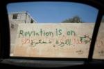 """كتابة على جدار في بلدة سرمين في إدلب تقول: """"الثورة مستمرة"""". إن محافظة إدلب في شمال غرب سوريا إحدى المناطق القليلة في سوريا الواقعة حالياً تحت سيطرة الجيش السوري الحر، على الرغم من أن هذه السيطرة غير مكتملة ومتحولة دوماً. سرمين، إدلب، سوريا."""