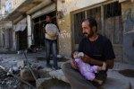 يجلس الرجل في مدينة عزاز شمالي سوريا مقابل بيته المخرّب في الشارع. يقوم بإرضاع ابنته بواسطة قنينة حليب. لقد تم طرد الجنود موالي الأسد من عزاز قبل ما يقارب الستة أشهر من الآن. ولكن الطيران الحربي السوري لا يزال مراراً وتكراراً ينفذ هجمات جوية على المدينة.