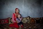 """سلمى، وهي أم سورية، تجلس مع طفلها في غرفة المعيشة المحترقة التي أصلحت جزئياً في البشيرية، إدلب، سوريا. في 22 أبريل/نيسان 2012، هاجم الجيش السوري وعصابة من """"الشبيحة"""" القرية، حيث داهموا المنازل وأحرقوها وأطلقوا النار عشوائياً وقصفوا المنطقة بالدبابات. وضع الجيش بندقية في رأس الطفل وأمر الأم بإعطاء معلومات عن الجيش السوري الحر."""