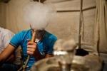 لاجئ سوري يدخن النرجيلة في مخيم يايلاداغي في هاتاي بجنوب تركيا. بلغ عدد اللاجئين الفارين من محافظة إدلب في الجارة سوريا أكثر من 20،000 وفقاً للحكومة التركية. 07/07/2012.