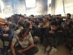 يجلس هؤلاء على الأرض مضمومي الأيدي وينظرون بخوف إلى حرّاسهم. تم التقاط هذه الصورة من قبل ناشطين سوريين. تظهر هذه الصورة على ما يبدو مقاتلين من جانب النظام السوري تم أسرهم من قبل المتمرّدين في جسر الشغور شمال البلاد. من غير المعروف ما إذا حصل قتال بين هؤلاء مع المتمرّدين من قبلُ أم أنهم كانوا مدنيين.