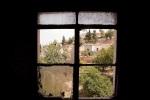 """المنظر من نافذة في منزل دوهم وأحرق على يد الجيش السوري عندما وصل إلى بلدة ليج، محافظة إدلب، سوريا. قصفت المنطقة على نطاق واسع ودوهمت من قبل الجيش السوري وميليشيات """"الشبيحة"""" الموالية للحكومة في الأشهر الأخيرة."""