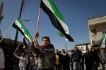 متظاهرون يهتفون لتغيير النظام، ملوحين بالعلم السوري القديم كرمز للاحتجاج في بلدة الجنودية، سوريا.