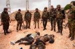 سوريون يقتلون سوريين. الجنود الثمانية الموالون للأسد يلقون نظرة على جثتين هامدتين ملتويتين لاثنين من المتمرّدين. لقيا حتفهما أثناء معارك حصلت في حلب.