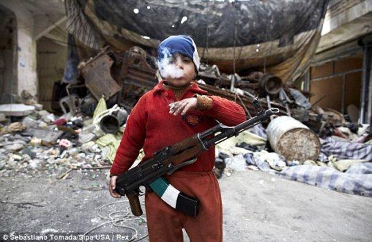 أطفال الحرب: التقطت الصورة أمام متراس / حاجز في حي صلاح الدين في حلب – عند الخطوط الأمامية للحرب الأهلية السورية الدامية.