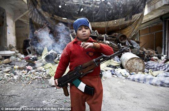 المحارب الصغير: أحمد، ذو السنين السبع، و ابن أحد مقاتلي الجيش السوري الحر، يقف أمام متراس / حاجز مساعداً رفاقه من الجيش السوري الحر في حي صلاح الدين.