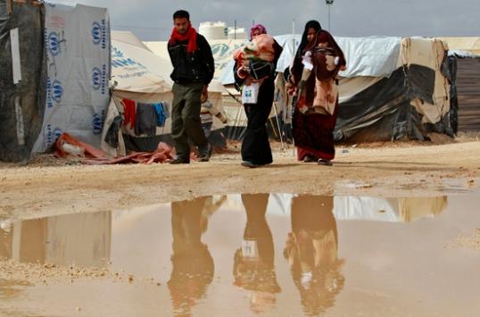 لاجئون السوريون يحملون أطفالهم في مخيم الزعتري للاجئين في مدينة المفرق الأردنية قرب الحدود مع سوريا يوم 12 شباط/فبراير 2013. (محمد حامد / رويترز)