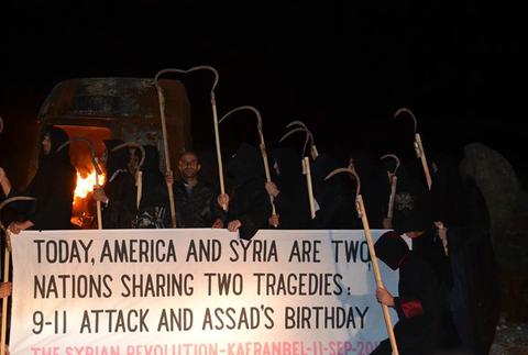 نشطاء في كفرنبل يرتدون زي الحداد أثناء احتجاج يوم 11 أيلول/سبتمبر، عيد ميلاد الرئيس السوري بشار الأسد.