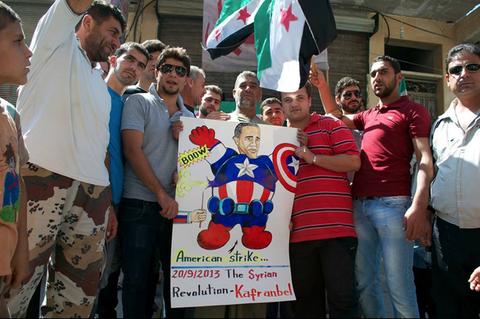 صور الرئيس أوباما بطلاً خارقاً نفست عضلاته المنتفخة بسهولة عن طريق دبوس، في مظاهرة في كفرنبل. ينتقد العديد من النشطاء السوريين الولايات المتحدة بسبب ما يصفونه بالدعم الباهتة للجماعات المتمردة في البلاد.