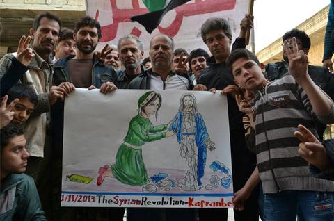 أظهر ملصق في احتجاج في كفرنبل امرأة، ترمز إلى سوريا، تعيد تجميع تمثالاً لمريم العذراء التي قيل أن أعضاء في دولة داعش قد دمرته.