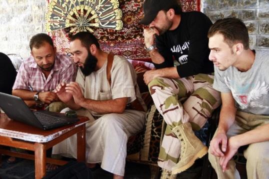جنود الجيش السوري الحر يشاهدون مقطع فيديو على شاشة الكمبيوتر المحمول. (حامد الخطيب / رويترز)
